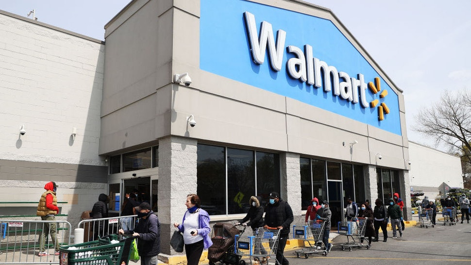 People wearing masks and gloves wait to enter a Walmart on April 17, 2020 in Uniondale, New York. The World Health Organization declared coronavirus (COVID-19) a global pandemic on March 11th. (Photo by Al Bello/Getty Images)