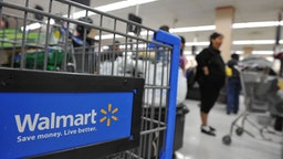 Shoppers wait in line to pay for their purchases at a Walmart store in Los Angeles, California on November 24, 2009, a few days before ÔøΩBlack FridayÔøΩ the day after Thanksgiving which kicks off the holiday shopping season. Retailers are hoping ÔøΩdoorbusterÔøΩ deals will stimulate sales despite the weak economy. AFP PHOTO / Robyn Beck