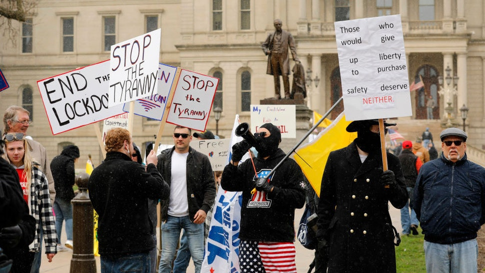 """A protest organized by """"Michiganders Against Excessive Quarantine"""" gathers around the Michigan State Capitol in Lansing, Michigan on April 15, 2020. - The group is upset with Michigan Governor Gretchen Whitmer's(D-MI) expanded the states stay-at-home order to contain the spread of the coronavirus. (Photo by JEFF KOWALSKY / AFP) (Photo by JEFF KOWALSKY/AFP via Getty Images)"""