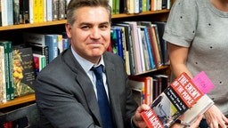 """WASHINGTON, D C , UNITED STATES - 2019/06/18: Jim Acosta holds his book """"The Enemy of the People: A Dangerous Time to Tell the Truth in America"""" at the Politics and Prose bookstore in Washington, DC. (Photo by"""