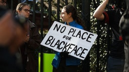 """Protestors rally against Virginia Governor Ralph Northam outside of the governors mansion in downtown Richmond, Virginia on February 4, 2019. - Demonstrators are calling for the resignation of Virginia Governor Ralph Northam, after a photo of two people, one dressed as a Klu Klux Klan member and a person in blackface were discovered on his personal page of his college yearbook. Northam said that while he had not appeared in the photo, """"many actions that we rightfully recognize as abhorrent today were commonplace"""" and he was not surprised such material made its way to the yearbook. (Photo by Logan Cyrus / AFP) (Photo credit should read"""