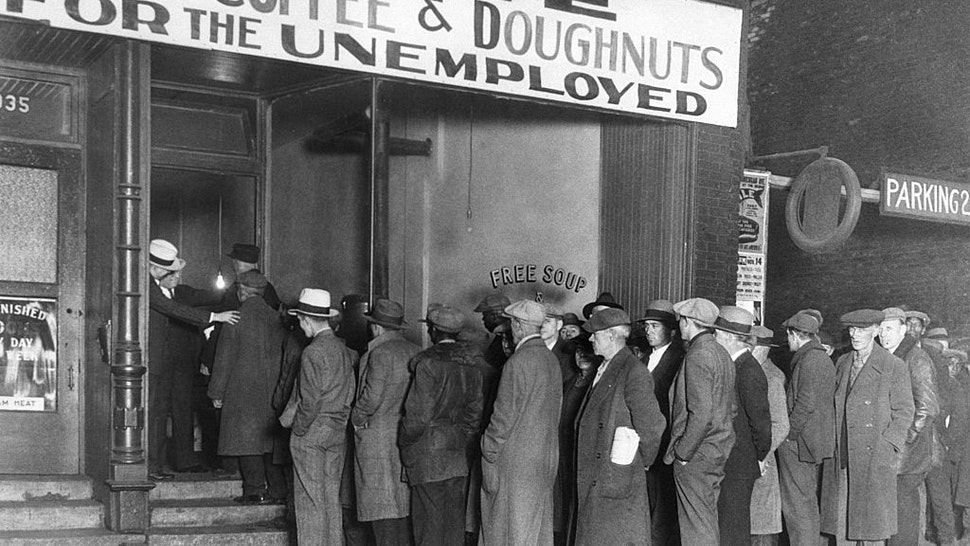 """Notorious gangster Al Capone attempts to help unemployed men with his soup kitchen """"Big Al's Kitchen for the Needy."""" The kitchen provides three meals a day consisting of soup with meat, bread, coffee, and doughnuts, feeding about 3500 people daily at a cost of $300 per day."""