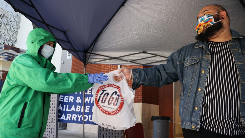 Real Food For Kids volunteer Rosemarie Wilson (L) and Silver Diner beverage manager Richard Torres work to hand out 400 free meals outside the restaurant during the coronavirus pandemic April 02, 2020 in Gaithersburg, Maryland.