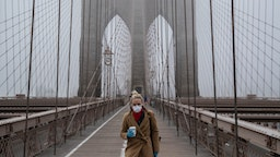 A woman wearing a mask walks the Brooklyn Bridge in the midst of the coronavirus (COVID-19) outbreak on March 20, 2020 in New York City.