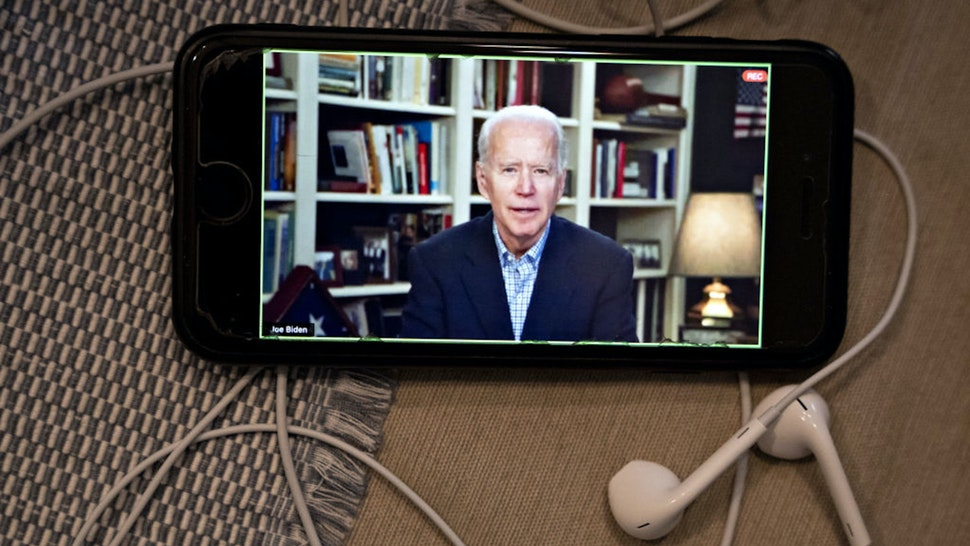 Former Vice President Joe Biden, 2020 Democratic presidential candidate, speaks during a virtual press briefing on a smartphone in this arranged photograph in Arlington, Virginia, U.S., on Wednesday, March 25, 2020. During the livestreamed news conference today, Biden said he didn't see the need for another debate, which the Democratic National Committee had previously said would happen sometime in April.
