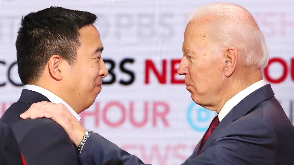 LOS ANGELES, CALIFORNIA - DECEMBER 19: Democratic presidential candidate Andrew Yang (L) speaks with former Vice President Joe Biden during the Democratic presidential primary debate at Loyola Marymount University on December 19, 2019 in Los Angeles, California. Seven candidates out of the crowded field qualified for the 6th and last Democratic presidential primary debate of 2019 hosted by PBS NewsHour and Politico.