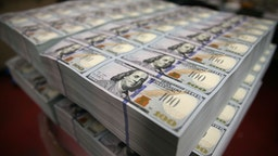 Newly redesigned $100 notes lay in stacks at the Bureau of Engraving and Printing on May 20, 2013 in Washington, DC.