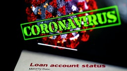 """In this photo illustration, a loan statement account status is displayed next a iPhone screen behind reading """"coronavirus"""" on April 16, 2020, in Arlington, Virginia. - The $349 billion cap for small business loans for the coronavirus stimulus was reached on April 16, 2020, taking less than two weeks to run out."""