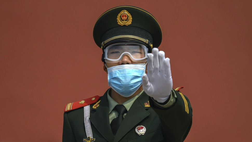 BEIJING, CHINA - MAY 01: A Chinese paramilitary police officer gestures as he wears a protective mask while standing guard at the entrance to the Forbidden City as it re-opened to limited visitors for the May holiday, on May 1, 2020 in Beijing, China. Beijing lowered its risk level after more than three months Thursday in advance of the May holiday, allowing most domestic travellers arriving in the city to do so without having to do 14 days quarantine. The Forbidden City opened to a limited number of visitors Friday morning for the first time in more than three months. After decades of growth, officials said China's economy had shrunk in the latest quarter due to the impact of the coronavirus epidemic. The slump in the worlds second largest economy is regarded as a sign of difficult times ahead for the global economy. While industrial sectors in China are showing signs of reviving production, a majority of private companies are operating at only 50% capacity, according to analysts. With the pandemic hitting hard across the world, officially the number of coronavirus cases in China is dwindling, ever since the government imposed sweeping measures to keep the disease from spreading. Officials believe the worst appears to be over in China, though there are concerns of another wave of infections as the government attempts to reboot the worlds second largest economy. Since January, China has recorded more than 81,000 cases of COVID-19 and at least 3200 deaths, mostly in and around the city of Wuhan, in central Hubei province, where the outbreak first started.