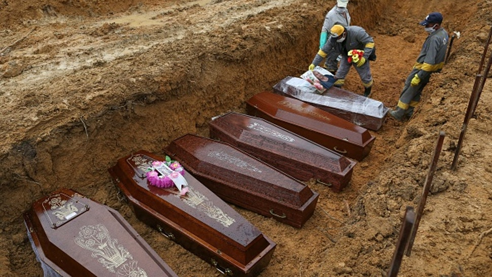 TOPSHOT - Cemetery workers prepare the coffins to be buried in a mass grave at the Nossa Senhora cemetery in Manaus, Amazon state, Brazil on May 6, 2020, amid the COVID-19 coronavirus pandemic.