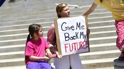 """HARRISBURG, PA - MAY 15: A girl holds a placard stating """"Give Me Back My Future"""" during a rally outside the Pennsylvania Capitol Building concerning the continued closure of businesses due to the coronavirus pandemic on May 15, 2020 in Harrisburg, Pennsylvania. Pennsylvania Governor Tom Wolf has introduced a color tiered strategy to reopen the state with most areas not easing restrictions until June 4."""