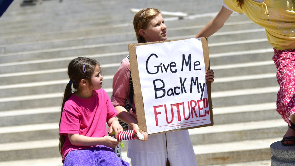"HARRISBURG, PA - MAY 15: A girl holds a placard stating ""Give Me Back My Future"" during a rally outside the Pennsylvania Capitol Building concerning the continued closure of businesses due to the coronavirus pandemic on May 15, 2020 in Harrisburg, Pennsylvania. Pennsylvania Governor Tom Wolf has introduced a color tiered strategy to reopen the state with most areas not easing restrictions until June 4."