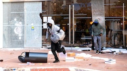 """People are seen looting stores at the Grove shopping center in the Fairfax District of Los Angeles on May 30, 2020 following a protest against the death of George Floyd, an unarmed black man who died while while being arrested and pinned to the ground by the knee of a Minneapolis police officer. - Clashes broke out and major cities imposed curfews as America began another night of unrest Saturday with angry demonstrators ignoring warnings from President Donald Trump that his government would stop violent protests over police brutality """"cold."""""""