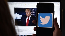 """In this photo illustration, a Twitter logo is displayed on a mobile phone with President Trump's Twitter page shown in the background on May 27, 2020, in Arlington, Virginia. - US President Donald Trump threatened Wednesday to shutter social media platforms after Twitter for the first time acted against his false tweets, prompting the enraged Republican to double down on unsubstantiated claims and conspiracy theories. Twitter tagged two of Trump's tweets in which he claimed that more mail-in voting would lead to what he called a """"Rigged Election"""" this November. (Photo by Olivier DOULIERY / AFP)"""
