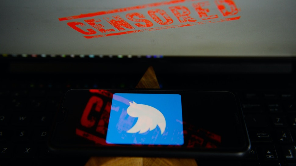 KRAKOW, POLAND - 2018/08/17: In this photo illustration, the Twitter logo is seen on a Huawei smartphone with the word censored on a laptop monitor. (Photo Illustration by Omar Marques/SOPA Images/SOPA Images/LightRocket via Getty Images)