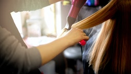 Young beautiful woman having her hair dried at hair salon