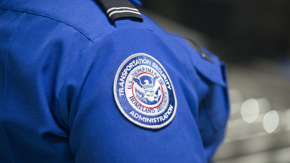 MIAMI, FLORIDA - MAY 21: A Transportation Security Administration (TSA) agent's patch is seen as she helps travelers place their bags through the 3-D scanner at the Miami International Airport on May 21, 2019 in Miami, Florida. TSA has begun using the new 3-D computed tomography (CT) scanner in a checkpoint lane to detect explosives and other prohibited items that may be inside carry-on bags. (Photo by Joe Raedle/Getty Images)