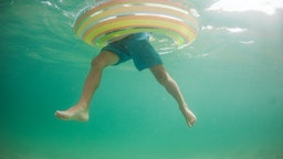Underwater view of a boy in an inflatable rubber ring, California, United States - stock photo