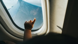 Cropped hand of a toddler pointing airplane window against blue sky while travelling - stock photo