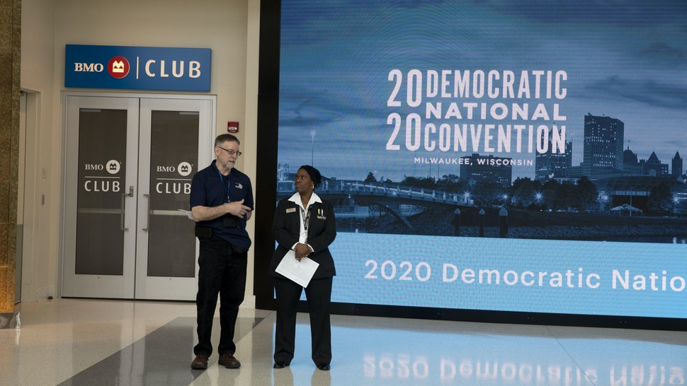 Workers stand near signage during a media walkthrough for the upcoming Democratic National Convention (DNC) at the Fiserv Forum in Milwaukee, Wisconsin, U.S., on Tuesday, Jan. 7, 2020. The 2020 DNC is scheduled to take place July 13-16. Photographer: Daniel Acker/Bloomberg via Getty Images
