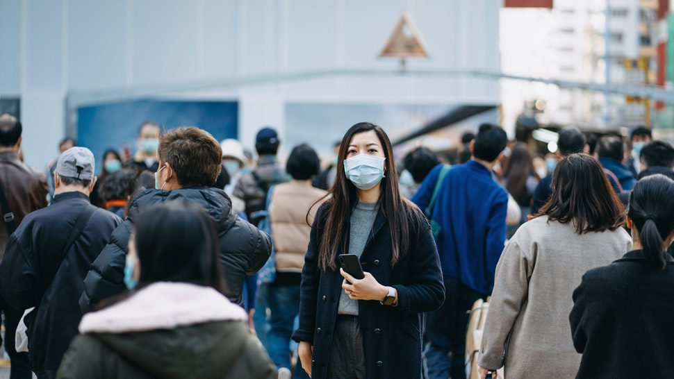Asian woman with protective face mask holding smartphone standing in the middle of busy downtown city street amidst crowd of pedestrians passing by