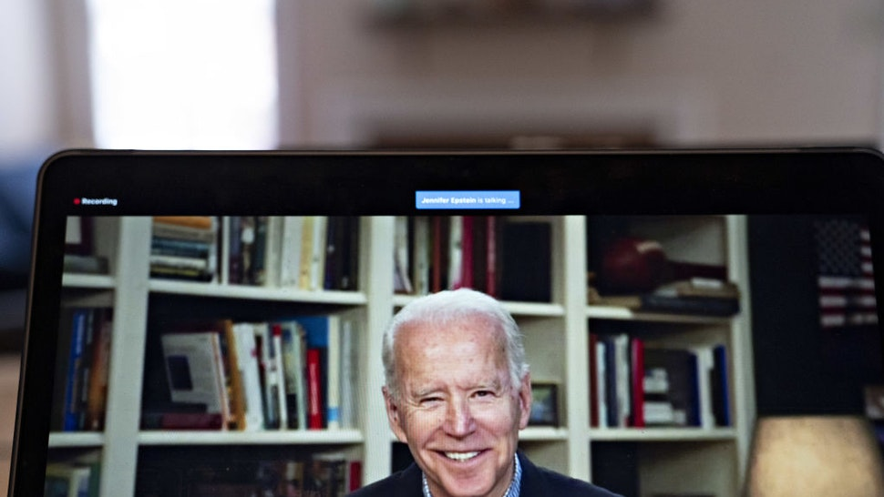 Former Vice President Joe Biden, 2020 Democratic presidential candidate, smiles during a virtual press briefing on a laptop computer in this arranged photograph in Arlington, Virginia, U.S., on Wednesday, March 25, 2020.