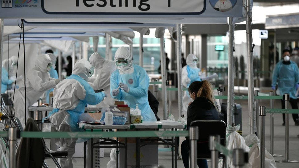 Medical staff wearing protective clothing take test samples for the COVID-19 coronavirus from a foreign passenger at a virus testing booth outside Incheon international airport, west of Seoul, on April 1, 2020.