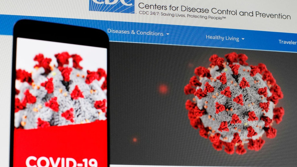 In this photo illustration the Centers of Disease Control and Prevention (CDC) web page displayed in internet on a pc screen and a coronavirus image on a mobile phone.