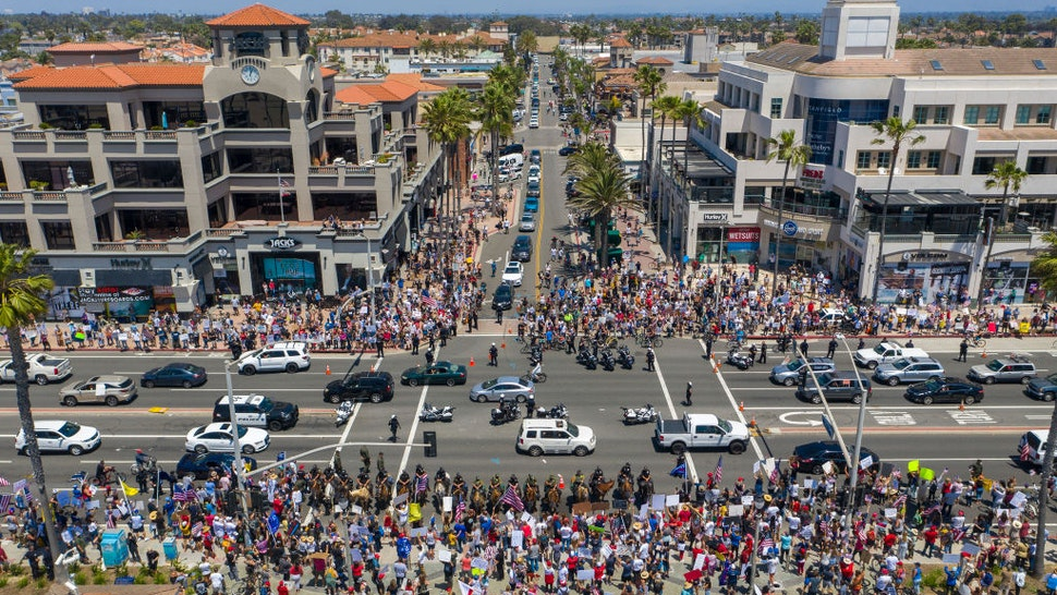 An aerial view shows a crowd of protesters calling to reopen businesses and beaches as the growing the coronavirus pandemic continues to cripple the economy on May 1, 2020 in Huntington Beach, California.
