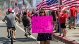 Protesters call to reopen businesses and beaches as the growing the coronavirus pandemic continues to cripple the economy on May 1, 2020 in Huntington Beach, California.