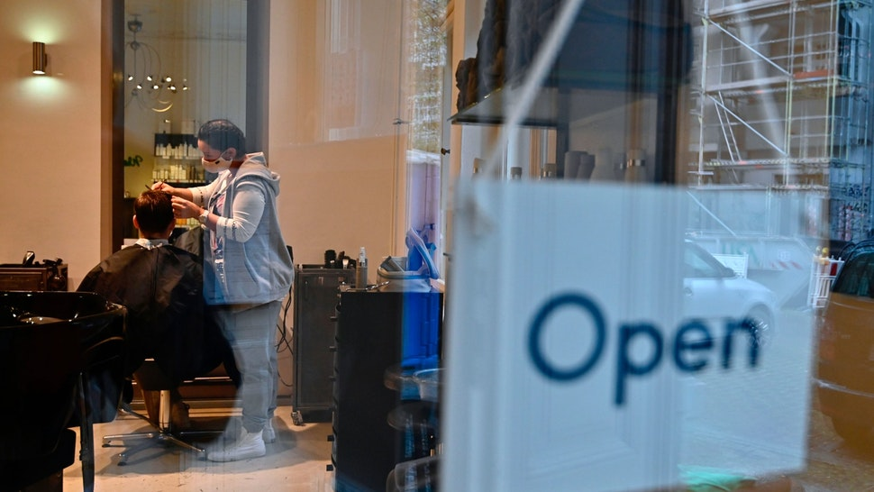 An open sign hangs in the window as a hairdresser cuts a customer's hair during the first day of reopening in Berlin on May 4, 2020 amid the novel coronavirus COVID-19 pandemic. (Photo by Tobias Schwarz / AFP) (Photo by TOBIAS SCHWARZ/AFP via Getty Images)