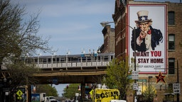 """A L train passes an """"I Want You To Stay Home"""" billboard in Chicago, Illinois, U.S., on Thursday, May 7, 2020."""