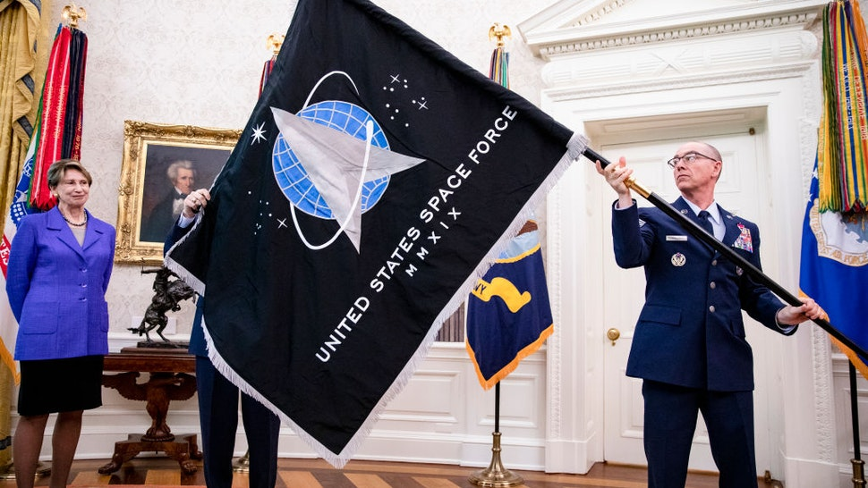 Gen. Jay Raymond (R), Chief of Space Operations, and CMSgt Roger Towberman (L), with Secretary of the Air Force Barbara Barrett present US President Donald Trump with the official flag of the United States Space Force in the Oval Office of the White House in Washington, DC on May 15, 2020.