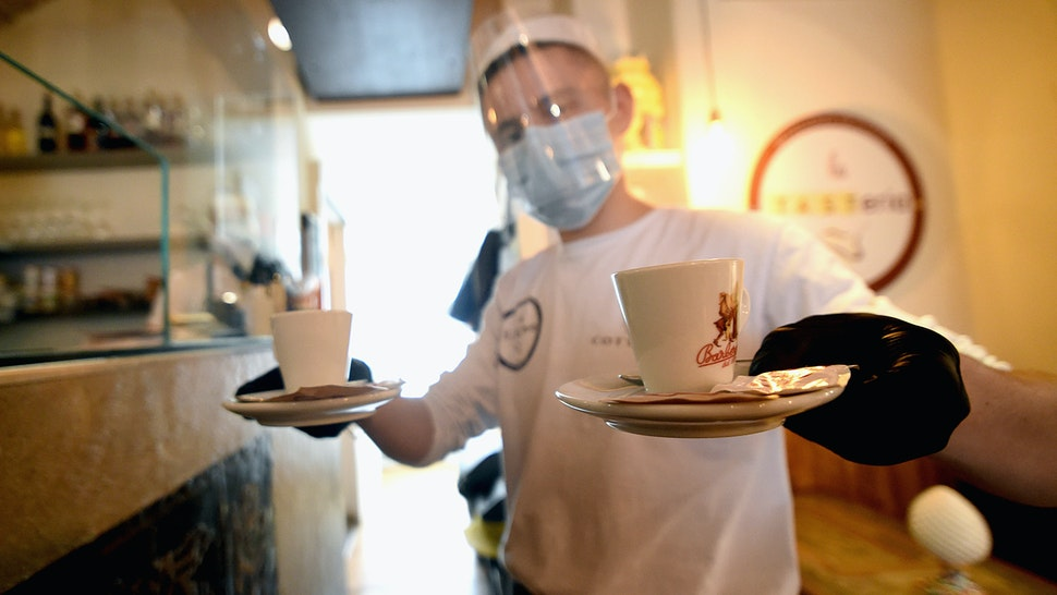 MILAN, ITALY - MAY 18: A waiter from the bistro 'La Tasteria' wearing a protective plexiglass mask brings two coffees to the table on May 18, 2020 in Milan, Italy. Restaurants, bars, cafes, hairdressers and other shops have reopened, subject to social distancing measures, after more than two months of a nationwide lockdown meant to curb the spread of Covid-19. (Photo by Pier Marco Tacca/Getty Images)