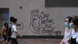 """Graffiti reading """"One Nation, One Hong Kong"""" is marked on a wall during a protest against a planned national security law in the Causeway Bay district in Hong Kong, China, on Sunday, May 24, 2020. Almost 200 politicians and legislators from 23 countries issued a joint statement criticizing Chinas plans to impose a sweeping national security law in Hong Kong, and warned that it could spark more protests in the city, Radio and Television Hong Kongreported. Photographer: Roy Liu/Bloomberg via Getty Images"""