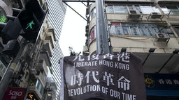 """A demonstrator raises a flag reading """"Liberate Hong Kong, Revolution of Our Time"""" during a protest in Hong Kong, China, on Wednesday, May 27, 2020. Officers fired pepper spray projectiles in downtown Hong Kong and arrested at least 16 people as protesters hit the streets Wednesday to oppose China's increasing control over the city, a return to unrest largely unseen since last year. Photographer: Justin Chin/Bloomberg via Getty Images"""