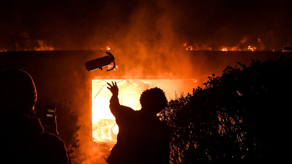 A protester throws a fire extinguisher in a burning building during a demonstration in Minneapolis, Minnesota, on May 29, 2020, over the death of George Floyd, a black man who died after a white policeman kneeled on his neck for several minutes. - Violent protests erupted across the United States late on May 29 over the death of a handcuffed black man in police custody, with murder charges laid against the arresting Minneapolis officer failing to quell seething anger. (Photo by Chandan KHANNA / AFP)