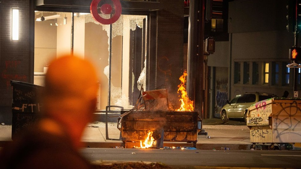 A dumpster is lit on fire infront of a Target store in Oakland California on May 30, 2020, over the death of George Floyd, a black man who died after a white policeman kneeled on his neck for several minutes.