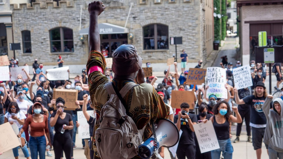 Myron Hollister Haynes (holding megaphone) speaks to protesters during a Mass Action for Black Liberation protest and march from Washington Park to City Hall following the alleged murder of George Floyd, Saturday, May 30, 2020, in Cincinnati, Ohio, United States.