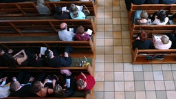 Congregation at church praying - stock photo