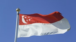 Close up of singaporean flag against blue sky, low angle view - stock photo