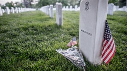 Tombstone at a World War II American military cemetery with a USA flag next to it
