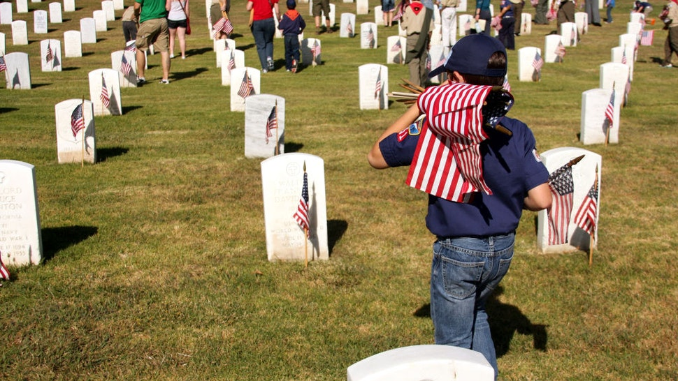 Cub Scout Carrying Flags to Place at Graves of Veterans on Memorial Day