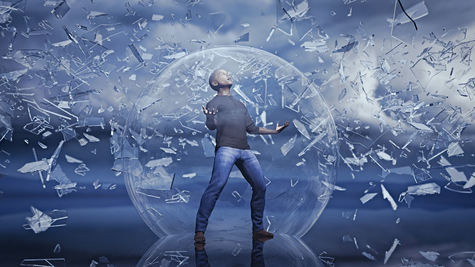 Man standing in sphere protected from falling shards of glass - stock photo