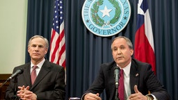Texas Gov. Greg Abbott, l, and Attorney General Ken Paxton hold a press conference to address a Texas federal court's decision on the immigration lawsuit filed by 26 states challenging President Obama. Paxton was indicted Monday on three counts of securities fraud unrelated to his official duties. (Photo by Robert Daemmrich Photography Inc/Corbis via Getty Images)