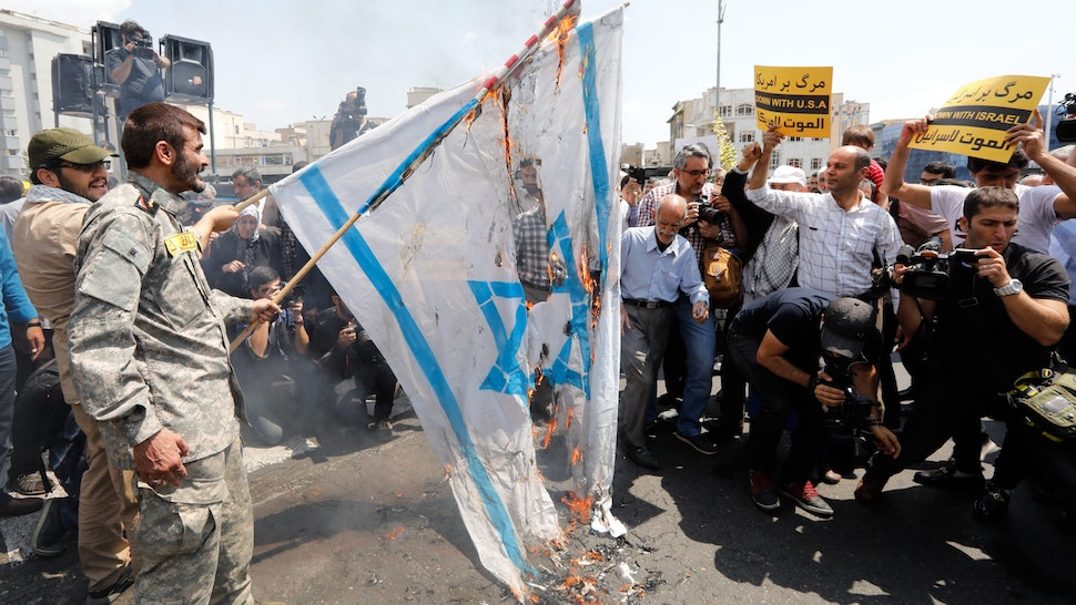 """Iranians burn a US and an Israeli flag as they take part in an anti-US and Israel demonstration after weekly Friday prayers in the capital Tehran on May 18, 2018, to show their solidarity with Palestinians over recent violent events in Gaza. The banners read in Farsi """"death to America""""."""