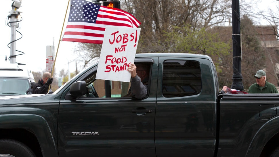 ALBANY, NY - APRIL 22: A protestor holds a sign out the window of their vehicle during an Operation Gridlock protest outside of the New York State Capitol Building on April 22, 2020 in Albany, New York. Protestors are calling on New York State Governor Andrew Cuomo to reopen New York State amidst a shutdown of all non-essential businesses due to the Coronavirus pandemic. (Photo by Stefani Reynolds/Getty Images)