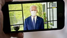 Former Vice President Joe Biden, presumptive Democratic presidential nominee, wears a protective mask during a NowThis economic address seen on a smartphone in Arlington, Virginia, U.S., on Friday, May 8, 2020. A super political action committee backing Joe Biden will launch a $10 million television ad campaign touting the presumptive Democratic nominee's leadership on the economic recovery after the 2008 financial crisis. Photographer: Andrew Harrer/Bloomberg via Getty Images