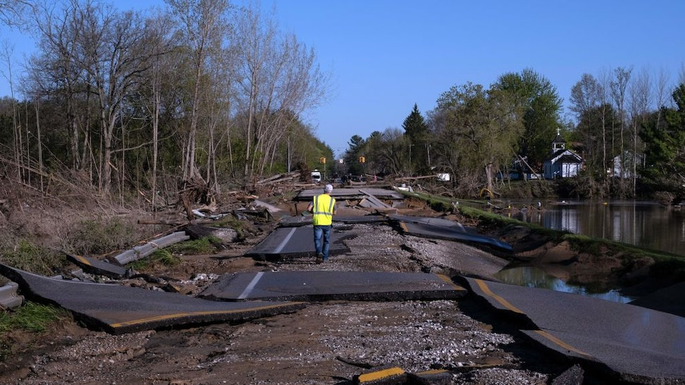 TOPSHOT - A man walks across a washed out West Saginaw Road in Sanford, Michigan, on May 21,2020, after the area saw heavy flooding and damage from heavy rains throughout central Michigan . - More than 10,000 residents were evacuating their homes in Michigan on May 20, 2020 after two dams failed following heavy rains triggered what officials warned will be historic flooding. Governor Gretchen Whitmer declared a state of emergency in Midland County, site of the breached dams, in the towns of Edenville and Sanford. (Photo by SETH HERALD / AFP) (Photo by SETH HERALD/AFP via Getty Images)