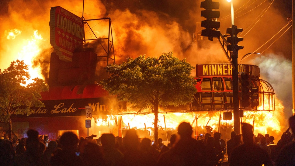 TOPSHOT - Protesters gather in front of a liquor store in flames near the Third Police Precinct on May 28, 2020 in Minneapolis, Minnesota, during a protest over the death of George Floyd, an unarmed black man, who died after a police officer kneeled on his neck for several minutes. - A police precinct in Minnesota went up in flames late on May 28 in a third day of demonstrations as the so-called Twin Cities of Minneapolis and St. Paul seethed over the shocking police killing of a handcuffed black man. The precinct, which police had abandoned, burned after a group of protesters pushed through barriers around the building, breaking windows and chanting slogans. A much larger crowd demonstrated as the building went up in flames.